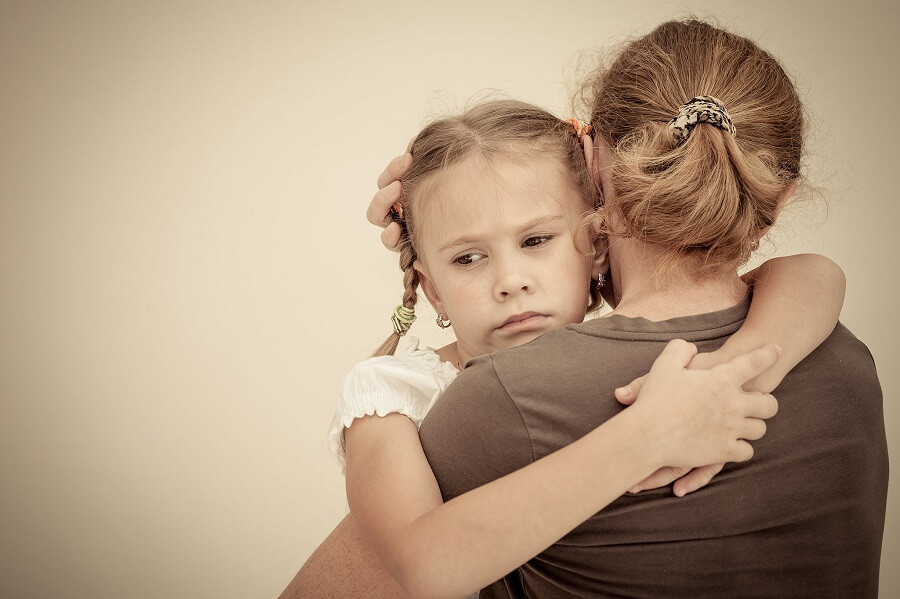 sad little girl hugging her mother