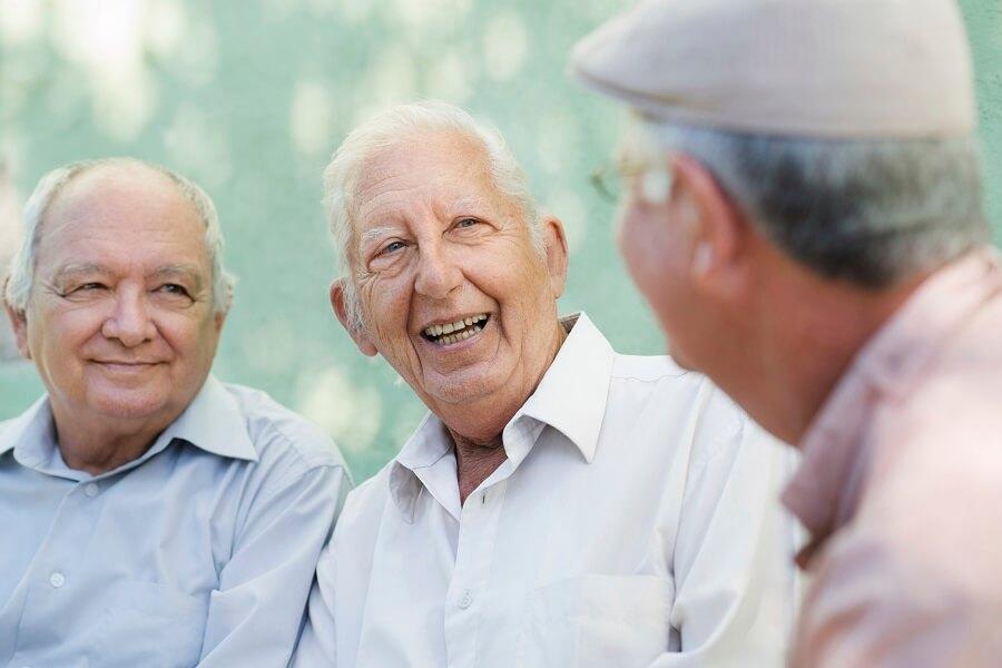 three elderly men laughing and talking