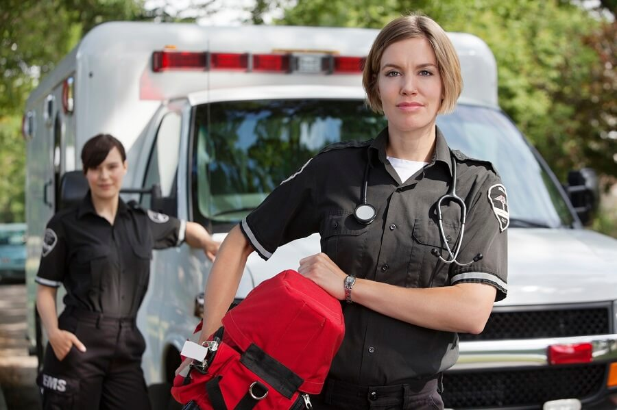 ambulance personnel posing in front of the ambulance