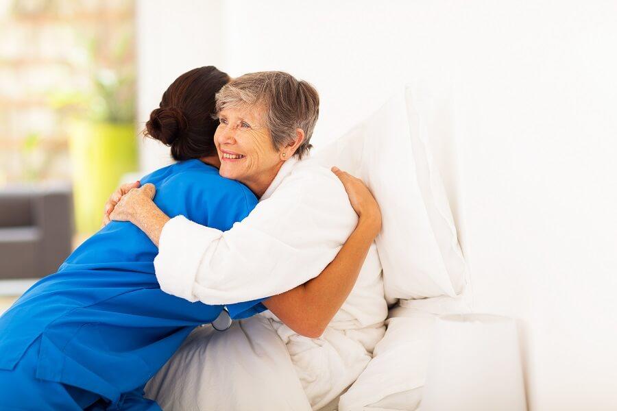 senior hugging a nurse and smiling