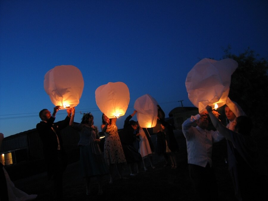 People lighting paper lanterns and launching them