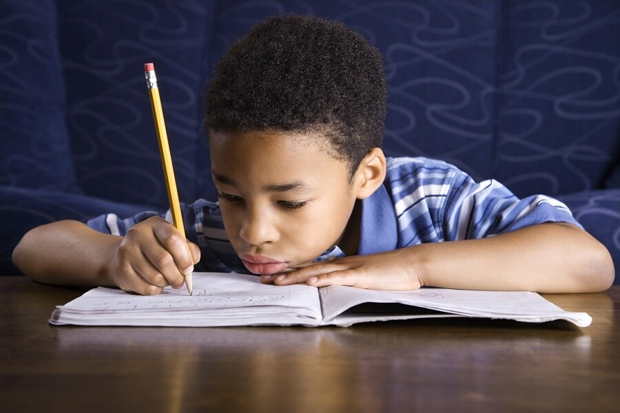 child looking sad and writing something in a notebook