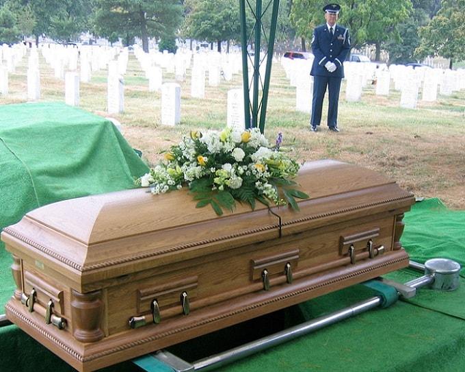 a brown casket with a flower arrangement