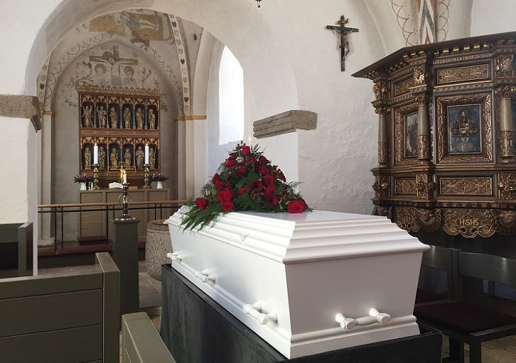 a white coffin in a church