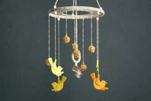 Handmade multicolor baby crib mobile with wooden birdies and rattan balls on gray background
