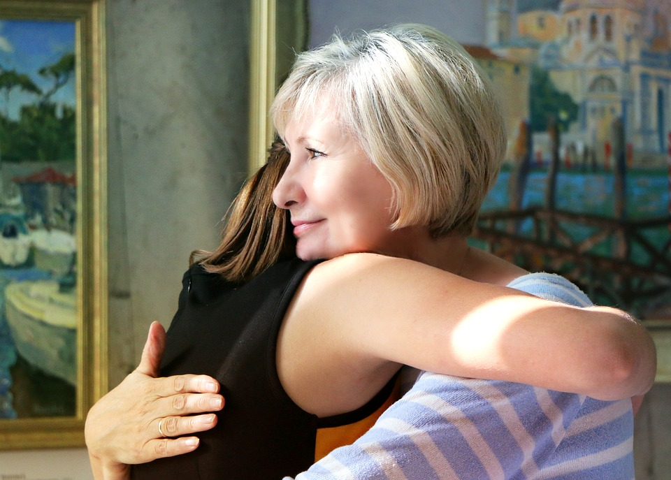 Older woman hugging a younger woman