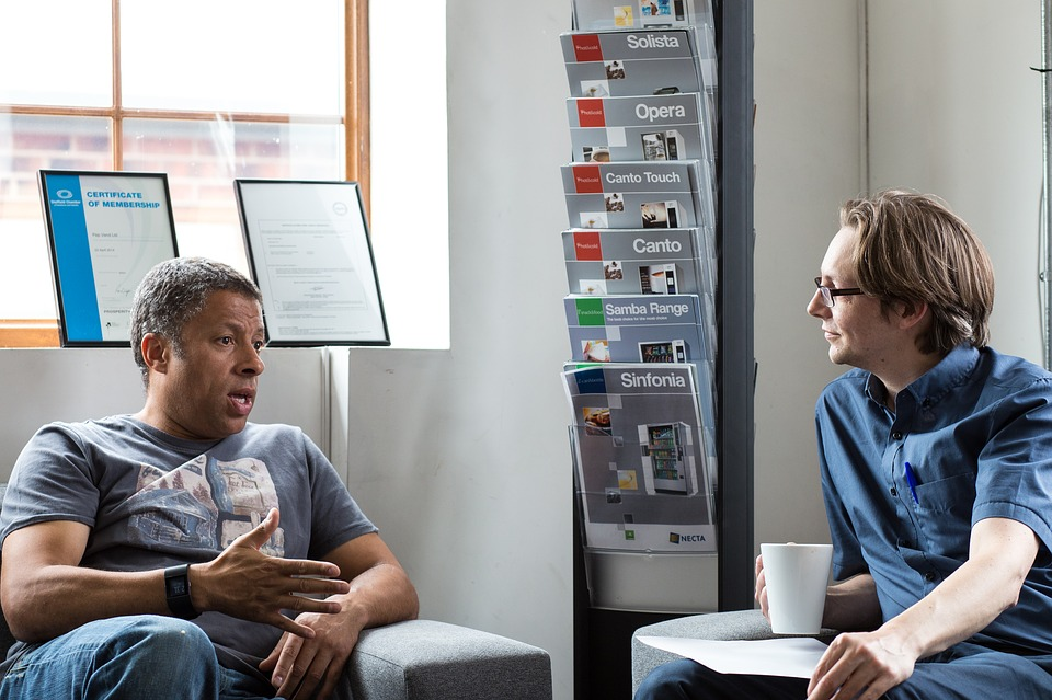 two men chatting in a public room