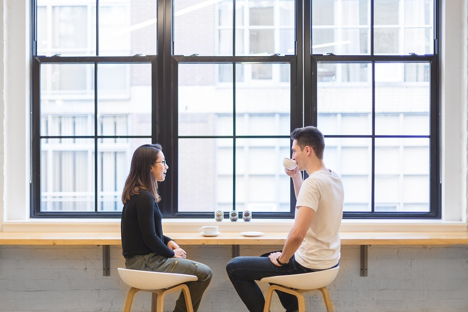 guy and girl talking in front of large window