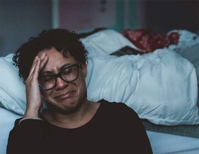 Woman crying beside the bed
